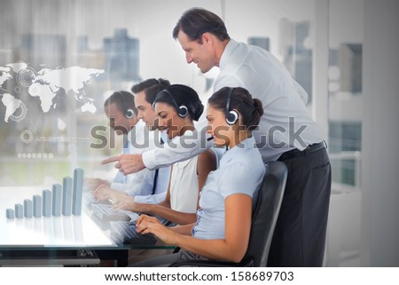 Call center employees at work on futuristic interfaces showing map and graph with supervisor in the office - stock photo