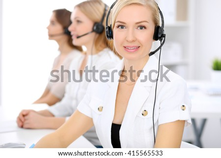 Call center. Focus on beautiful woman in headset - stock photo