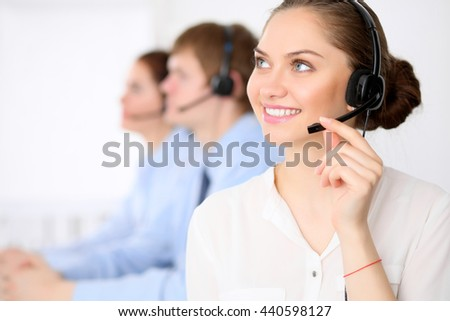 Call center operators. Young beautiful business woman in headset. Call center. Male call operator in headset at the background. - stock photo