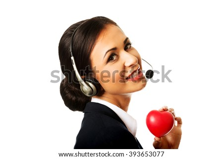 Call center woman holding heart model - stock photo
