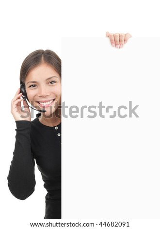 Call center woman with headset holding blank white billboard sign. Smiling and friendly young mixed race chinese / caucasian secretary or telemarketing assistant isolated on white background. - stock photo