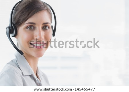 Call centre agent smiling at camera in an office - stock photo
