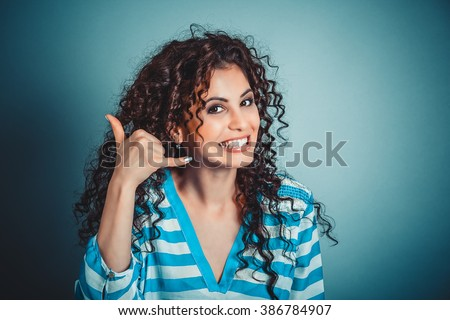 Call me. Closeup portrait headshot young woman pretty smiling curly hair girl white blue shirt showing call me sign hands gesture looking at you camera, retro vintage 50's hairstyle. Body language - stock photo