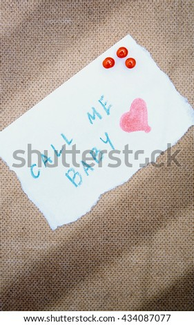 Call me written on a paper attached by pushpins to the wooden bulletin board - stock photo