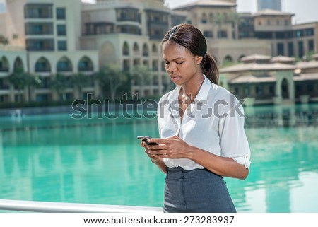 Call the customer. African businesswoman businessman holding a cell phone in hand and looking at it while standing near lake and looking at the camera - stock photo