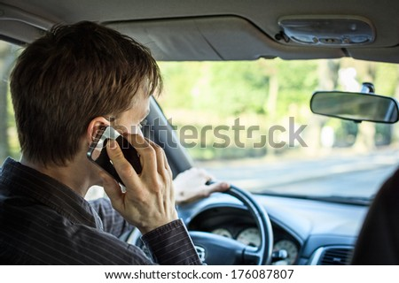 Calling on mobile while driving a car - stock photo