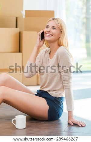 Calling you from my new house! Cheerful young woman sitting on the floor and talking on the mobile phone while cardboard boxes laying in the background - stock photo