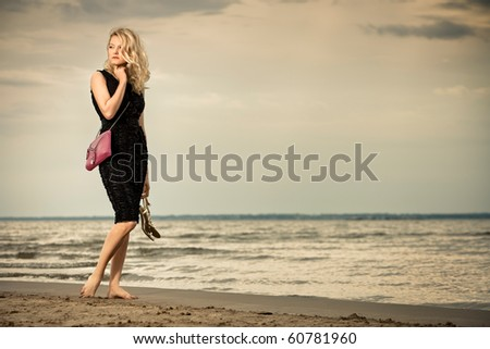 Calm and barefoot. Fashionable young woman in dress with handbag paddling on sandy beach. - stock photo