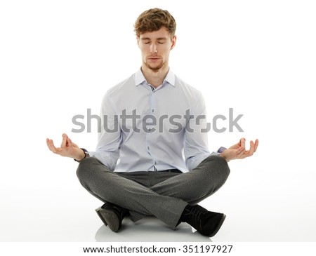 Calm and relaxed businessman meditating, sitting with his legs crossed - stock photo