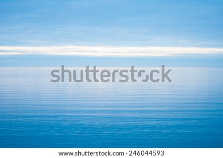 Calm and still open sea blurring into a cloudy blue sky - stock photo
