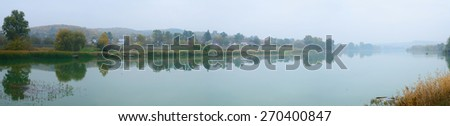 Calm autumn panoramic scene with yellow grass by the lake with village and reflections - stock photo