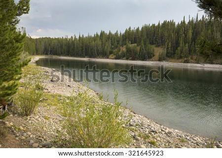 Calm bay of Jackson Lake near Hermitage Point, Grand Teton National Park, Wyoming. - stock photo