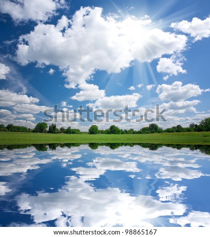 Calm beautiful rural landscape with a lake and sky reflected - stock photo