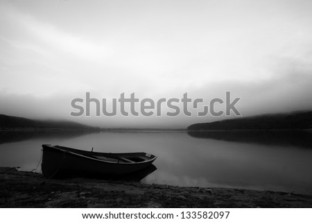calm black and white landscape with lake and lonely boat - stock photo