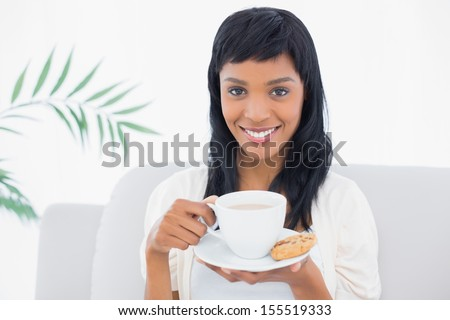 Calm black haired woman in white clothes drinking coffee in a living room - stock photo