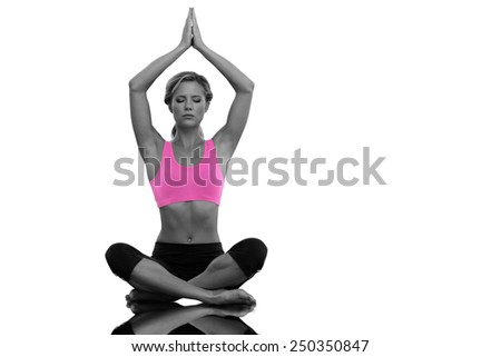 Calm blonde meditating in lotus pose with arms raised against mirror - stock photo