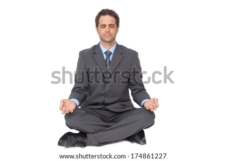 Calm businessman meditating in lotus pose on white background - stock photo