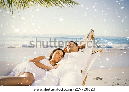 Calm couple napping in a hammock against snow falling - stock photo