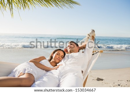 Calm couple napping in a hammock at the beach - stock photo
