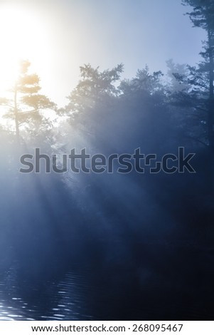 Calm Foggy Lake in the Morning with Beautiful Rays of Sunlight - stock photo