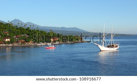 Calm lagoon with blue clear water with buildings on the coast and anchored sail boat - stock photo
