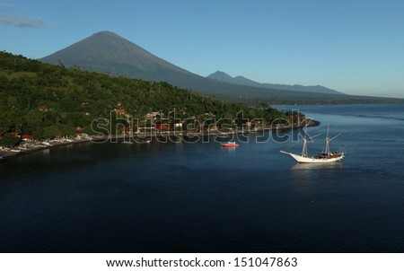 Calm lagoon with village on the coast and volcano (Agung) on the background. Bali, Indonesia - stock photo