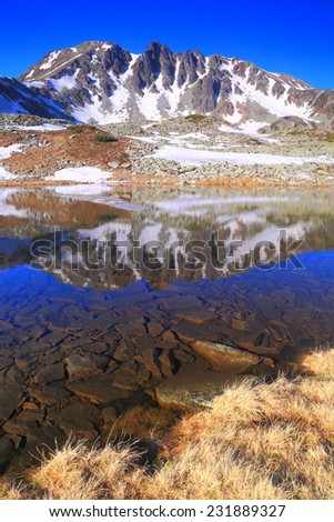 Calm lake reflects distant mountains early in the morning - stock photo