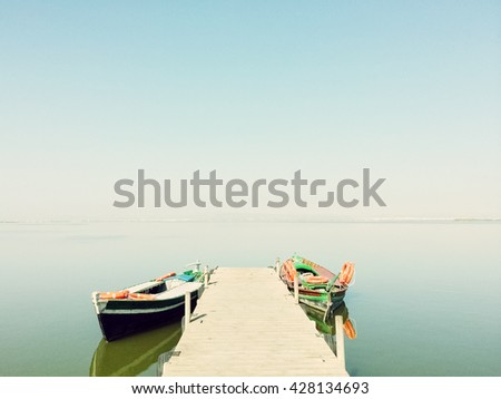 Calm lake with two fishing boats. Fresh water lagoon in Albufera de Valencia, Spain. - stock photo