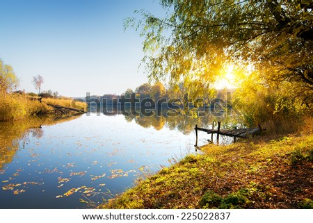 Calm river and autumn forest at sunrise - stock photo