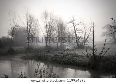calm river running through misty fields - stock photo