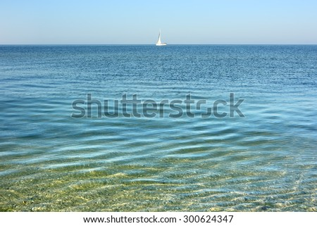 Calm sea surface. Seascape with sailing ship in early morning hours under clear skies. - stock photo