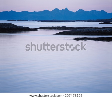 Calm Water and Distant Mountains - stock photo