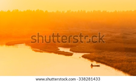 Calm Water Of Lake, River and rowing fishing boat at beautiful sunrise in autumn morning. Fisherman is in the boat - stock photo