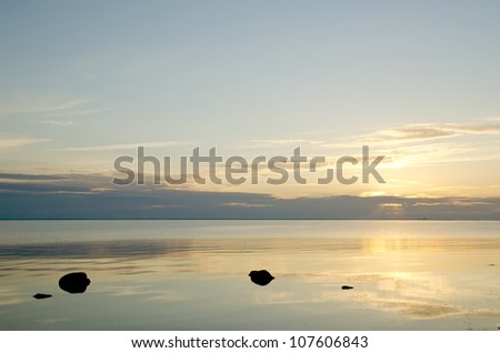 Calm water with black rocks in sunset - stock photo