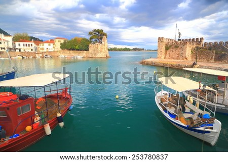Calm waters inside Nefpaktos harbor and fishing boats protected against stormy weather, Greece - stock photo