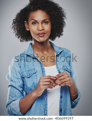 Calm woman wearing red nail polish and blue jean shirt against gray background - stock photo
