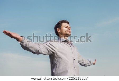 Calm young man portrait over blue sky - stock photo