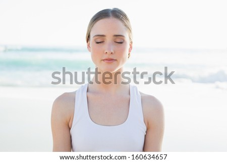 Calm young woman sitting on the beach with closed eyes - stock photo