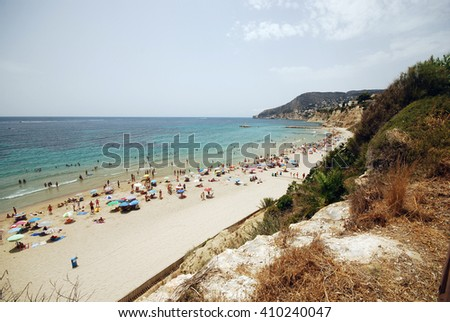 CALPE, SPAIN - AUGUST 8: Crowed beaches of Calpe August 8, 2012 in Calpe, Spain. Crowed beaches with a lot of tourists with the famous Ifach mountain on the background  - stock photo