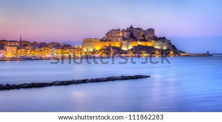 Calvi city illuminated at night with sea in foreground, Corsica Island, France. - stock photo