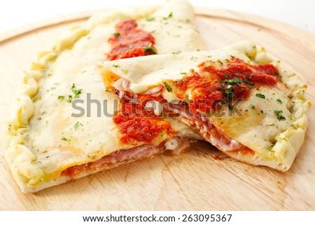 Calzone - Stuffed Pizza with Tomato, Mozzarella and Ham - stock photo