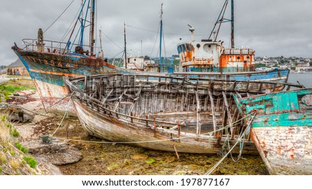 Camaret sur Mer's aged decaying wooden fishing fleet sits moored to the pier. The boats are weathered and rusty and falling apart. / Old Fishing Boats Decaying - stock photo