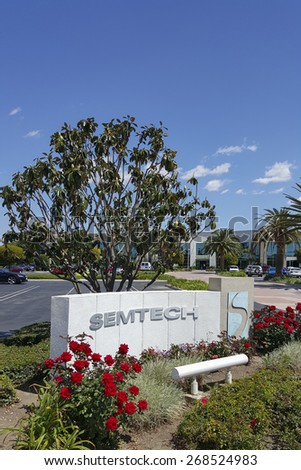 CAMARILLO, CA - APRIL 8, 2015: Hi-Tech company of Semtech front sign and logo with red roses in foreground and magnolia tree, palms and main road to the corporate headquarter office in Camarillo, CA - stock photo