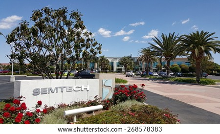 CAMARILLO, CA - APRIL 8, 2015: Semtech front sign and logo with red roses in foreground and magnolia tree, palms and main road to the corporate headquarter office in Camarillo, California - stock photo