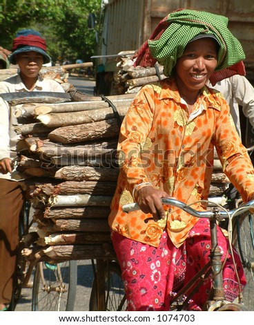Cambodian lady carrying timber on bicycle - stock photo