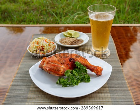 Cambodian style grilled chicken on white plate garnished with parsley ...