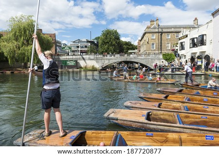 CAMBRIDGE, UK - AUGUST 18: Professional punter in Silver Street with busy River Cam full of tourists in gondolas in background. August 18, 2013 in Cambridge. - stock photo