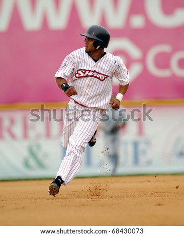 CAMDEN, NJ - AUGUST 15: Camden Riversharks infielder Juan Francia digs for third base after hitting a ball to the gap during an Atlantic League game August 15, 2010 in Camden, NJ. - stock photo