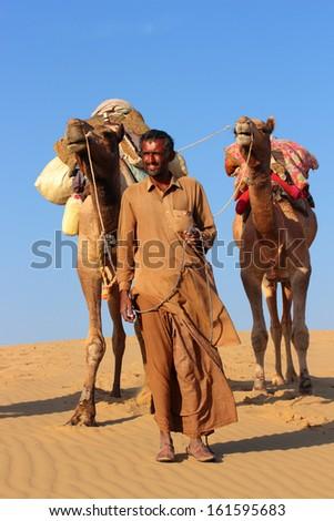 cameleer in desert - camels caravan on sand dune - stock photo