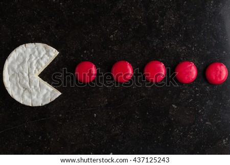 Camembert cheese and mini pieces on black background. Funny game with food, traditional French dish for wine on lunch and dinner closeup. - stock photo